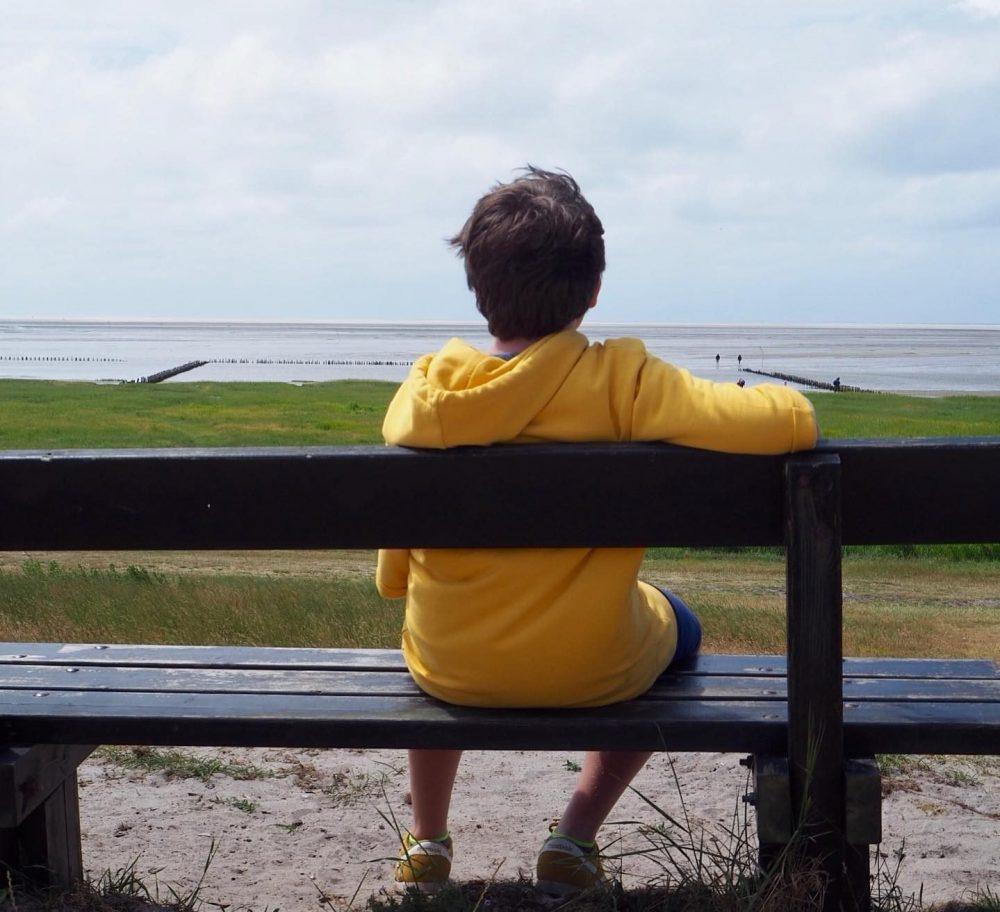 garcon sur un banc regardant la mer