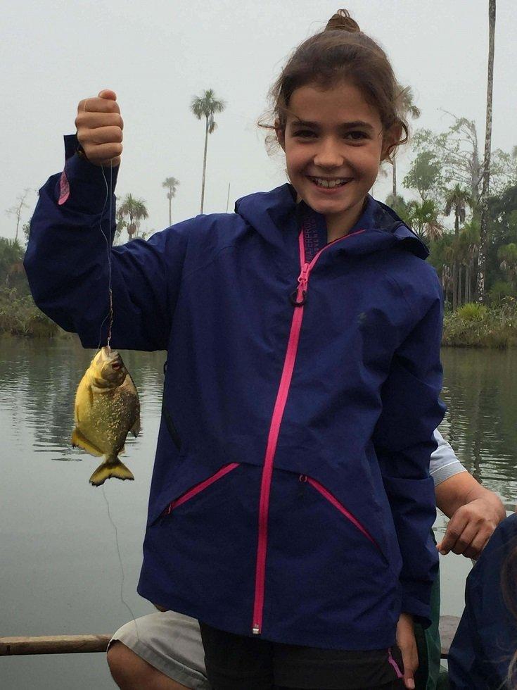 enfant en amazonie avec un piranha