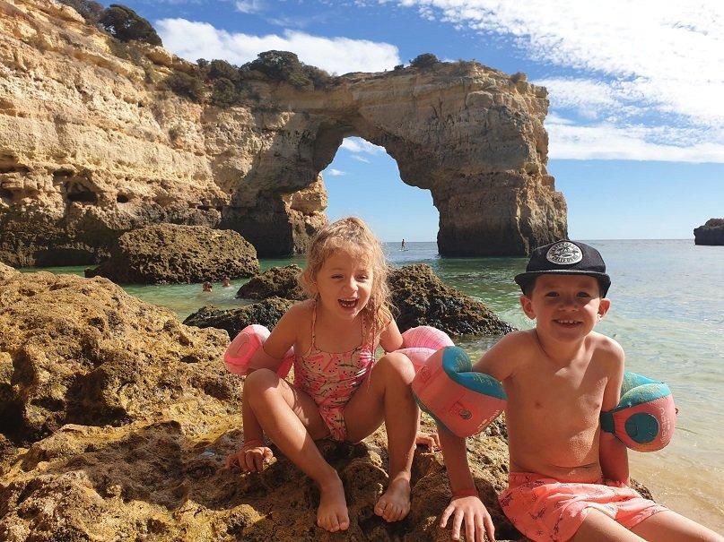 enfants sur une plage devant des falaises au portugal