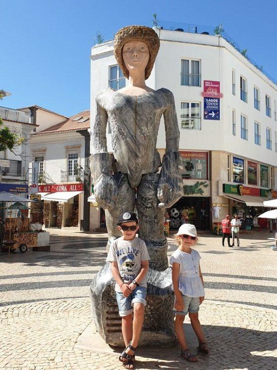 enfants devant une statue au portugal