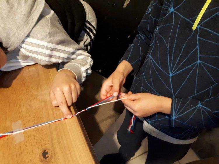 enfants fabricant un bracelet en laine