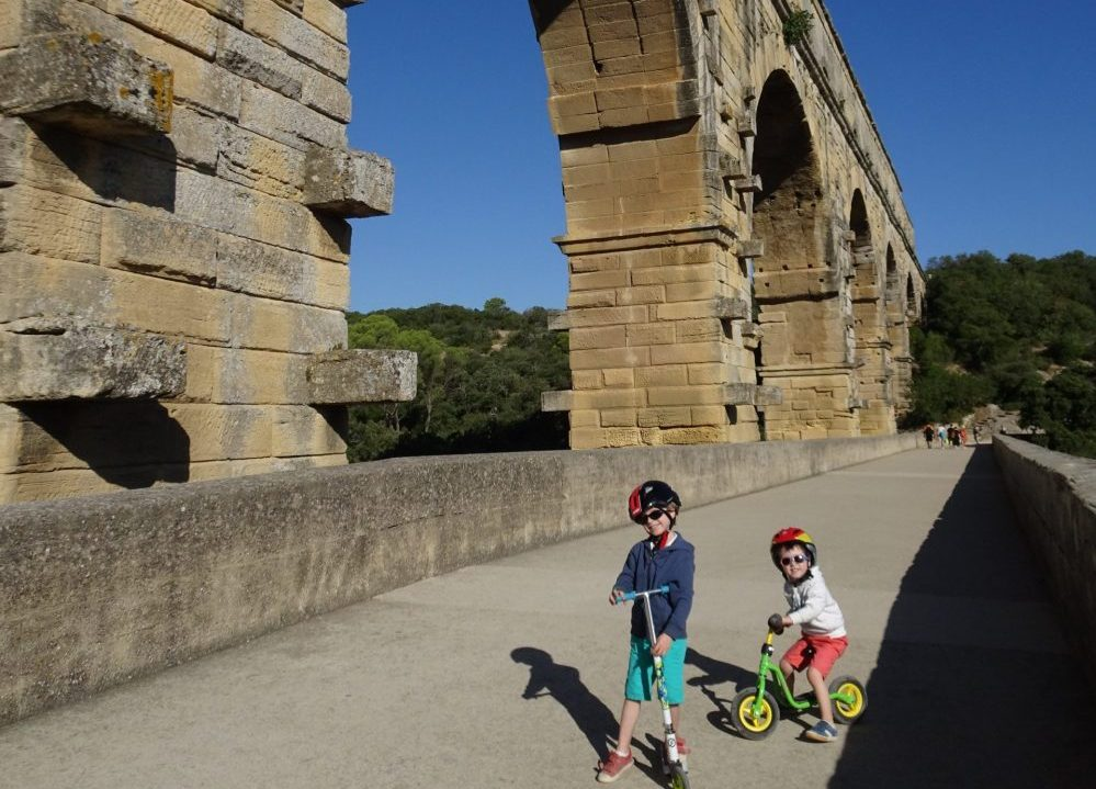enfants sur des vélos sous le pont du gard