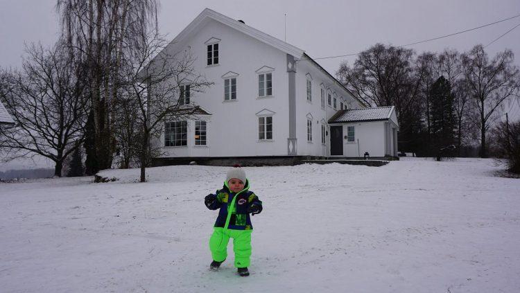 enfant dans la neige devant une maison