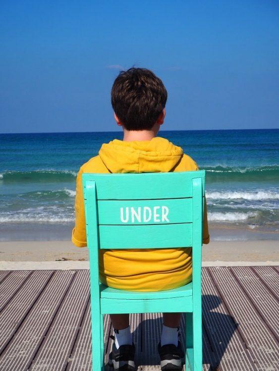 enfant assis sur une chaise qui regarde la mer