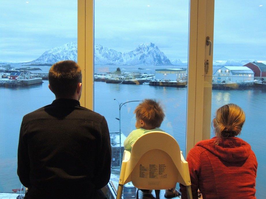 famille devant une fenêtre et vue sur la montagne